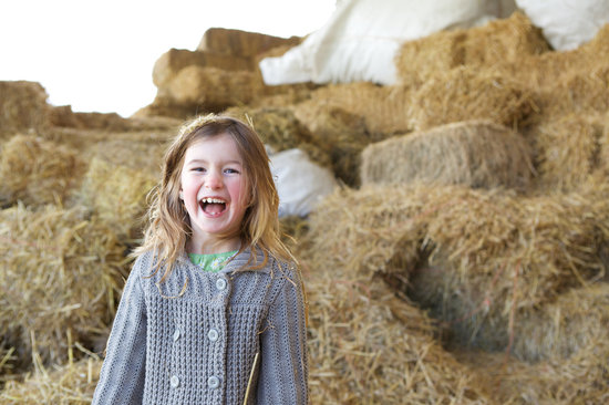 Close up portrait of a young girl laughing on farm with haystacks